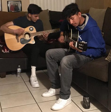 Roberto and Matthew Prado playing guitar.