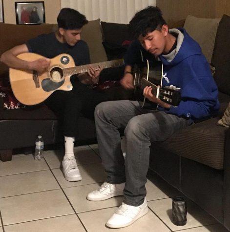 Roberto and Matthew Prado playing guitar.