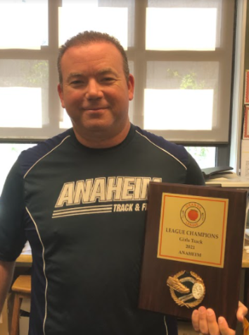 Coach Storm holding the Track and Field league champion award.
